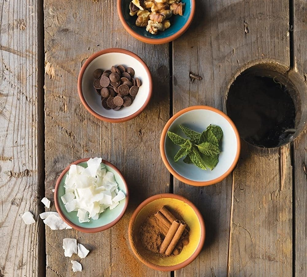 Five small bowls placed on a wooden background Each is filled with a different cooking ingredient like cinnamon, chocolate, mint, and granola