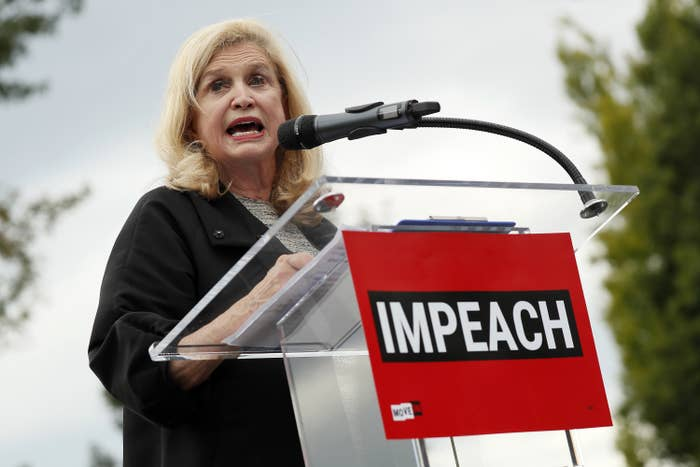 "Representative Carolyn Maloney speaks at a podium with the word ""Impeach"" written on it"