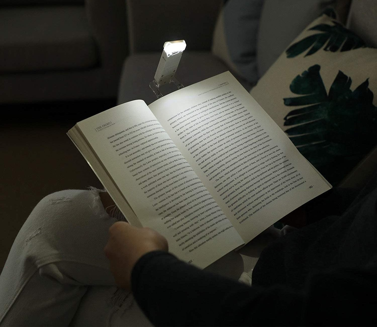 A person reading a large book in the dark There is a small book light attached to the top of the book
