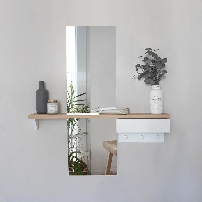 A full-length mirror with a wood shelf across the middle and a white drawer and hooks on the right side