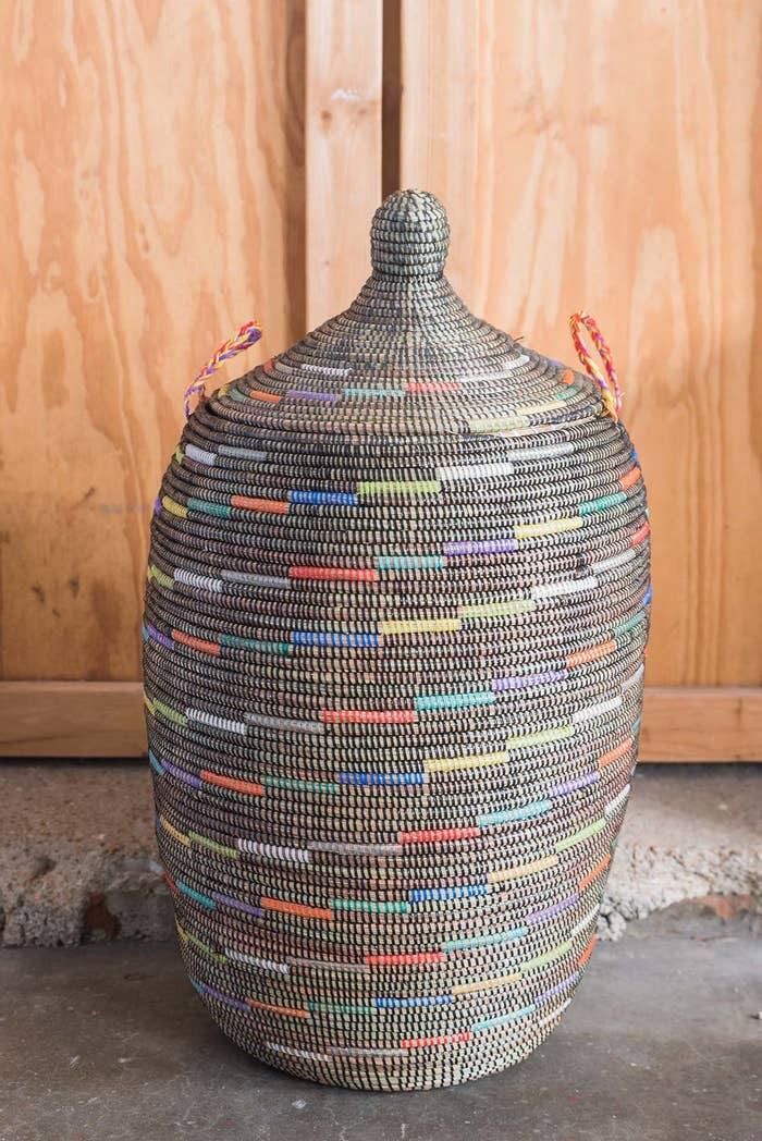 A large woven basket with a lid and handles on the side with black and multi-colored lines all over