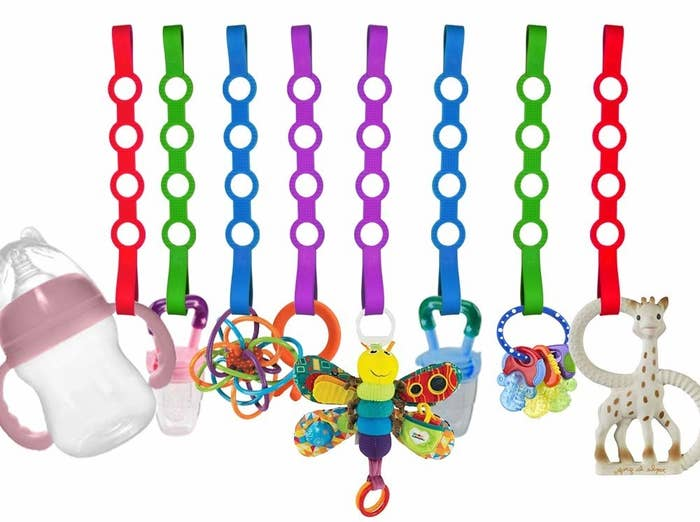 Multi-colored straps holding various baby toys and bottles