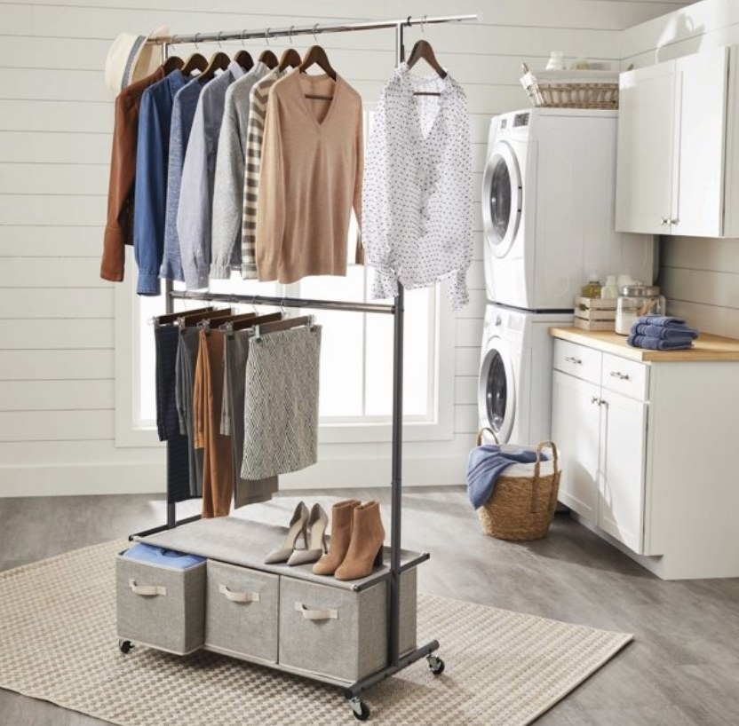 A metal-framed garment rack with two clothing bars and one shelf on black caster wheels