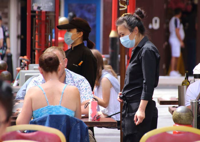 Server wearing a mask serves two people outside