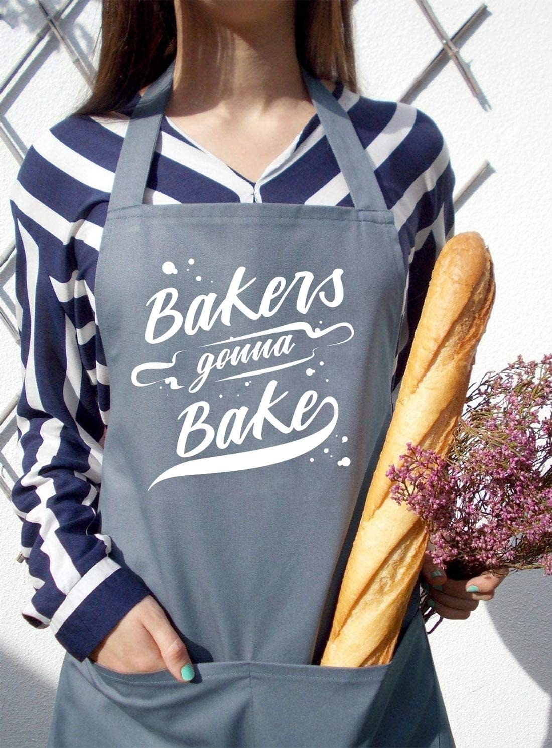 A person wearing an apron that says bakers gonna bake on it