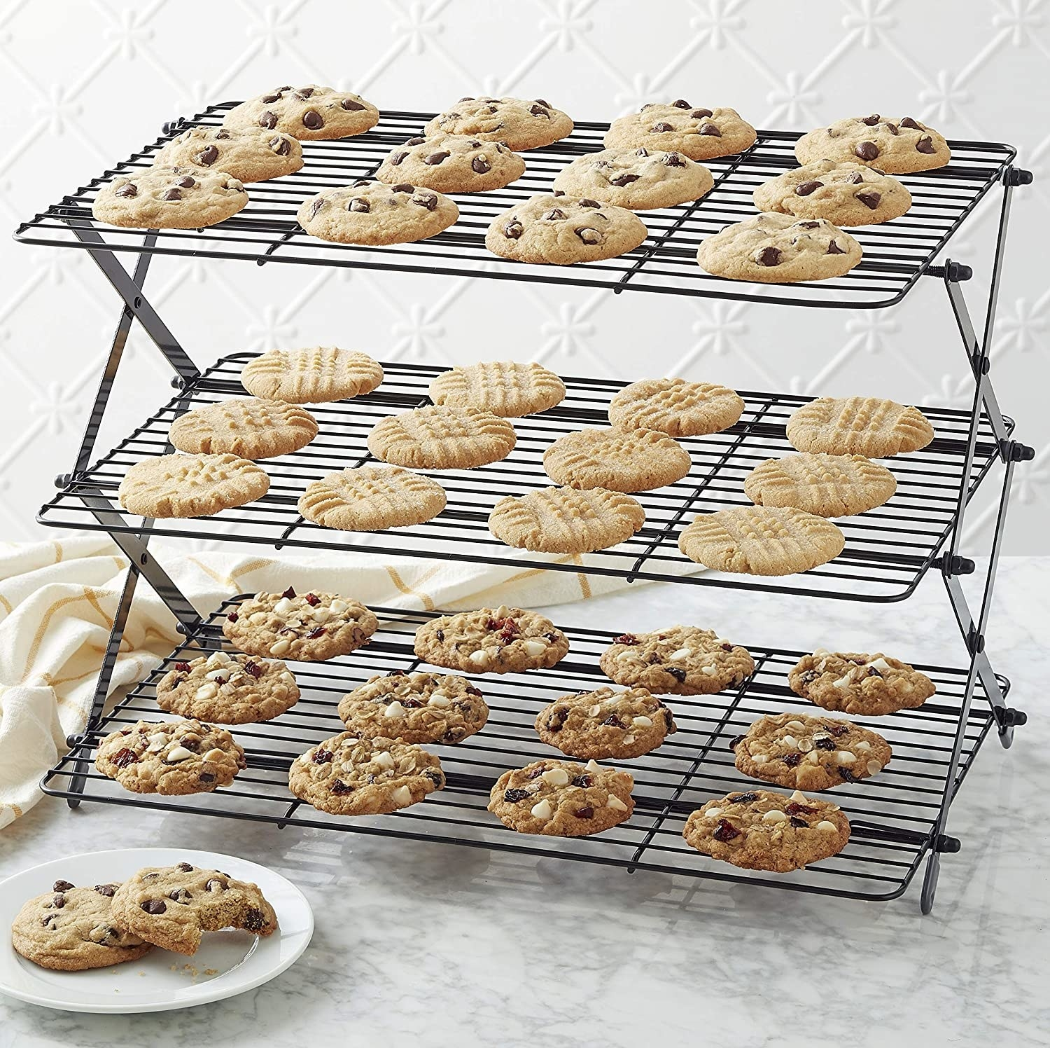 Three batches of cookies sitting on a three-tiered cooling rack