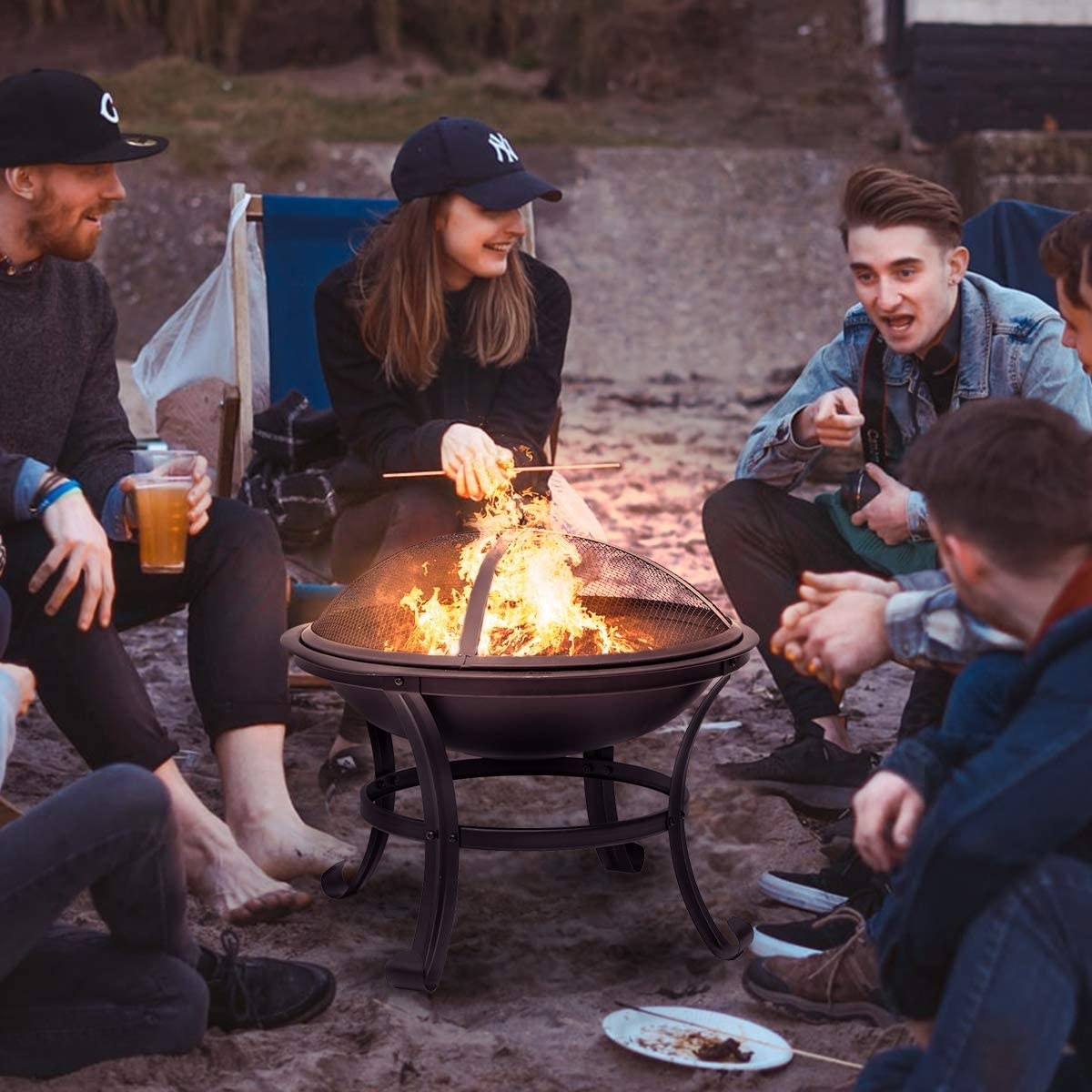 A group of people sitting around the elevated fire pit. The fire rises high above the gridded steal covering.