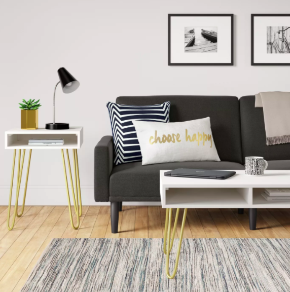 """Dark gray futon with a striped pillow and a pillow that says """"choose happy"""" next to a white coffee table with gold legs"""