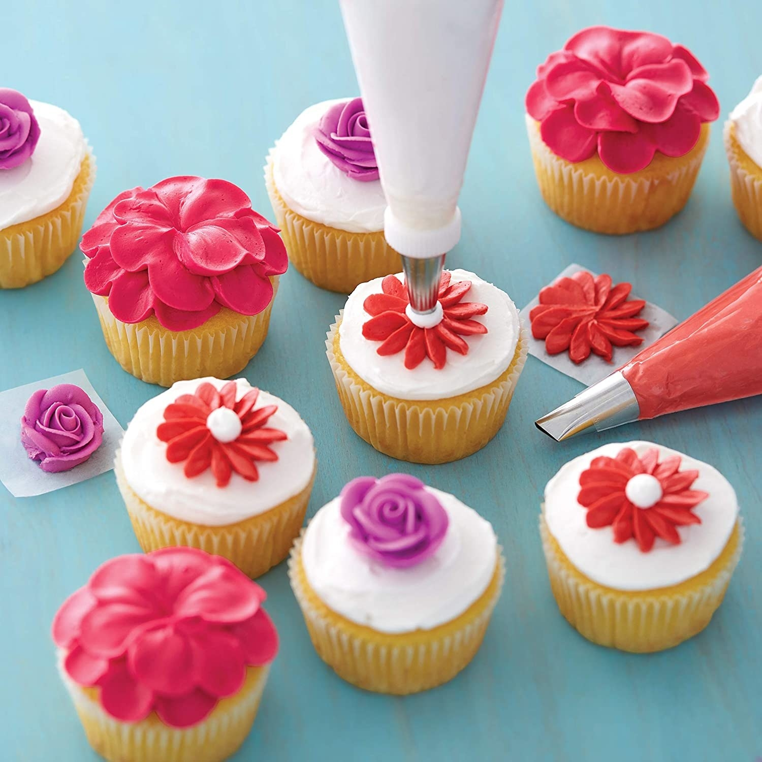 A person decorating a batch of cupcakes using a plastic decorating bag filled with icing