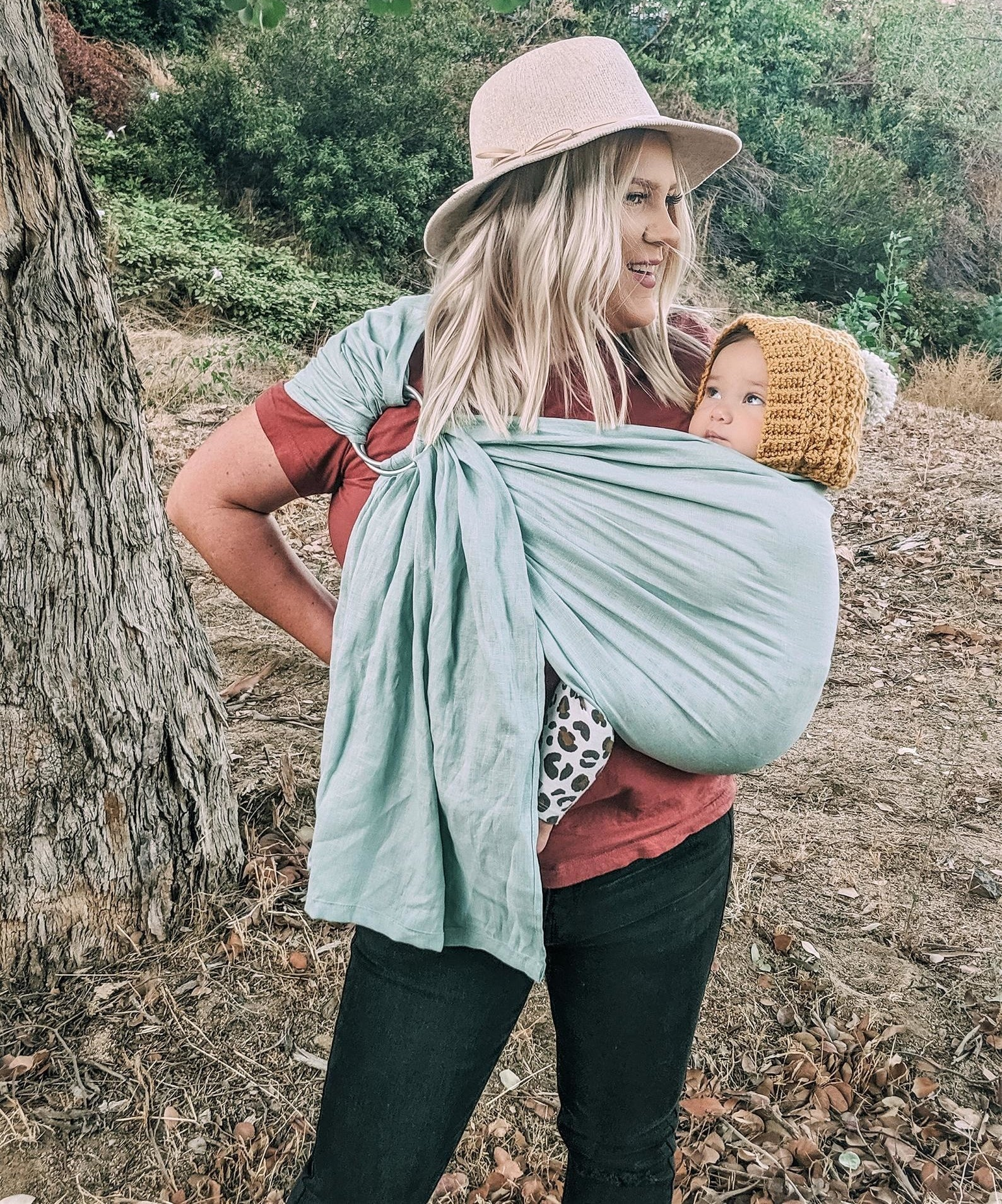 A parent carrying their child in a cool mint colored baby carrier