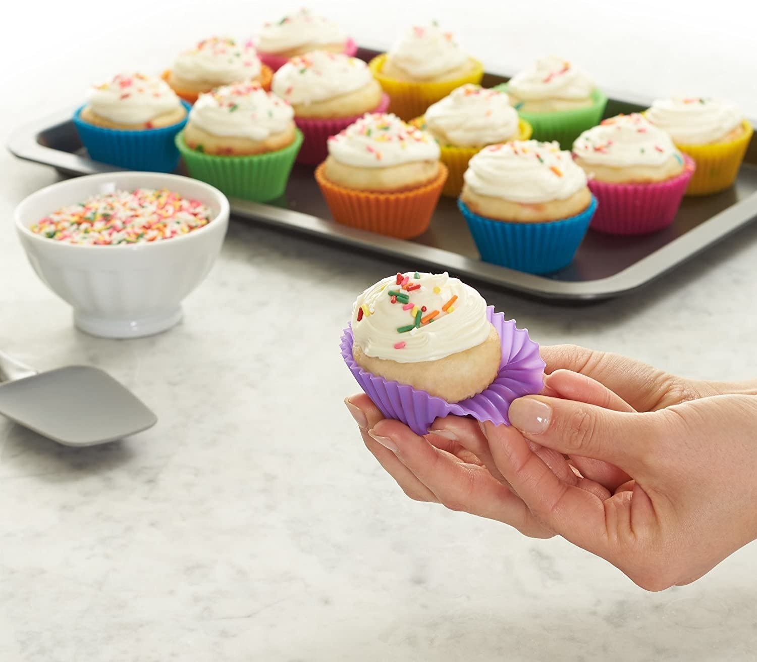 A person holding a tiny cupcake with a silicone baking cup