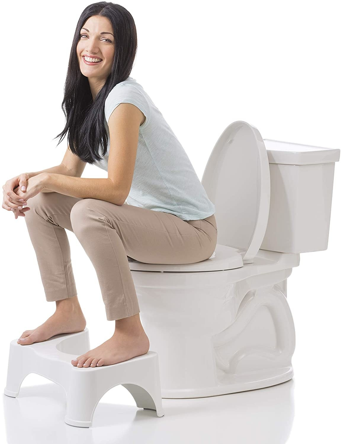 A model sitting on the toilet with their feet propped up on the white stool underneath it