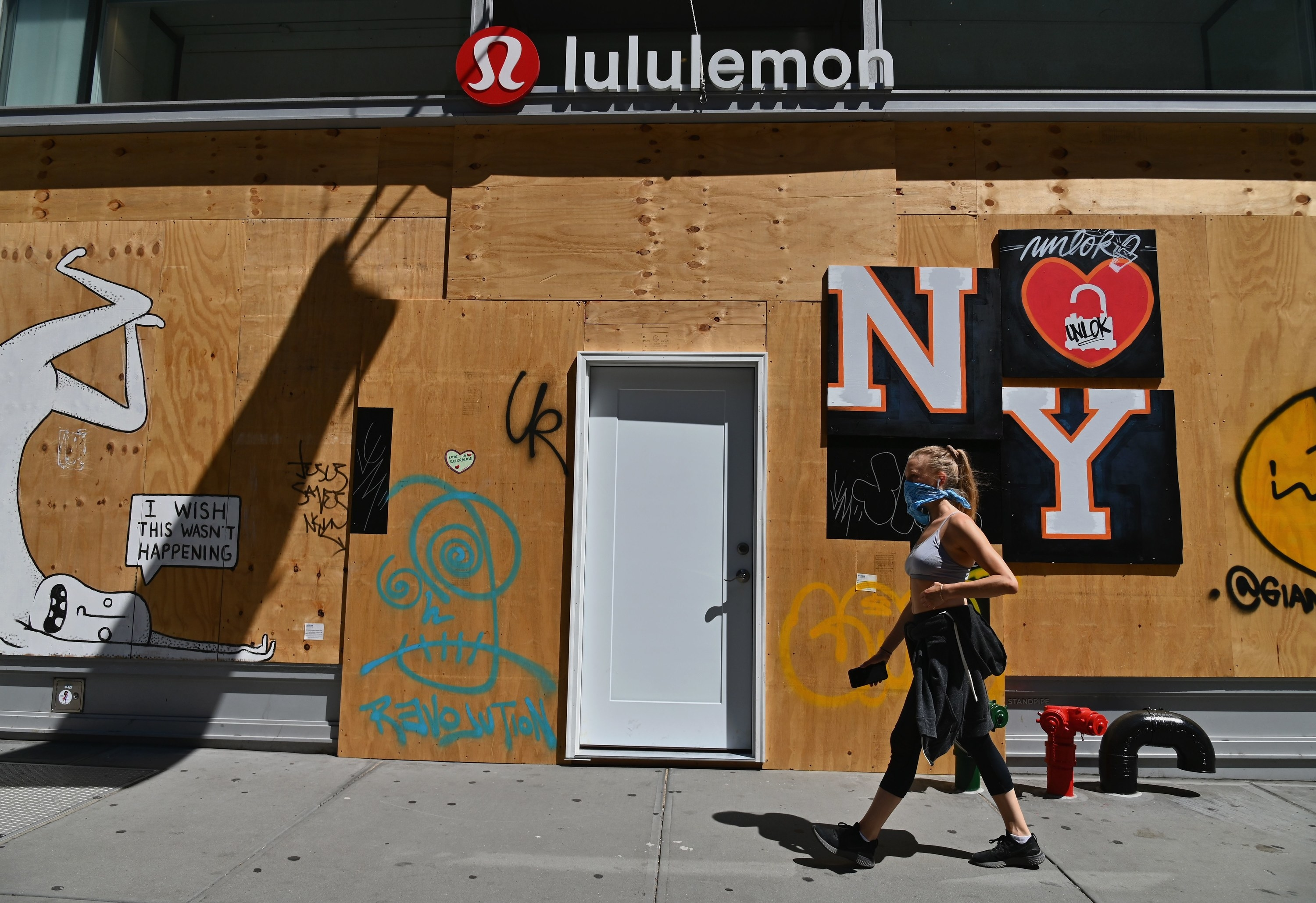 "A woman wearing a face-covering walks past a boarded-up Lululemon storefront with a poster attached to it featuring a heart and ""NY"""