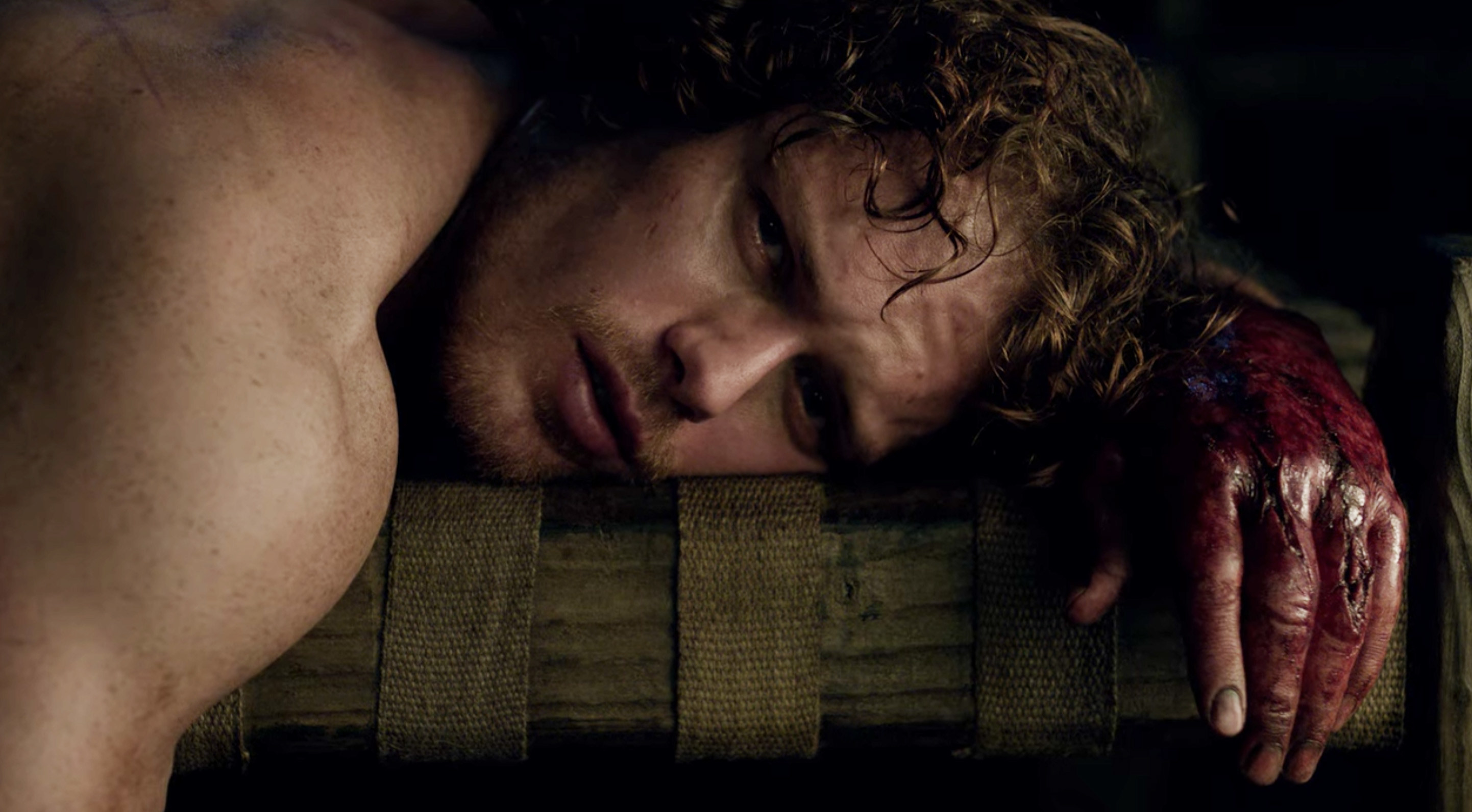 Jamie crying and lying on a bed with a bloody hand