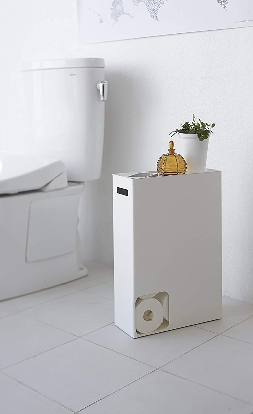 A white rectangle holder with a small square cut out in the bottom left corner, revealing rolls of toilet paper inside