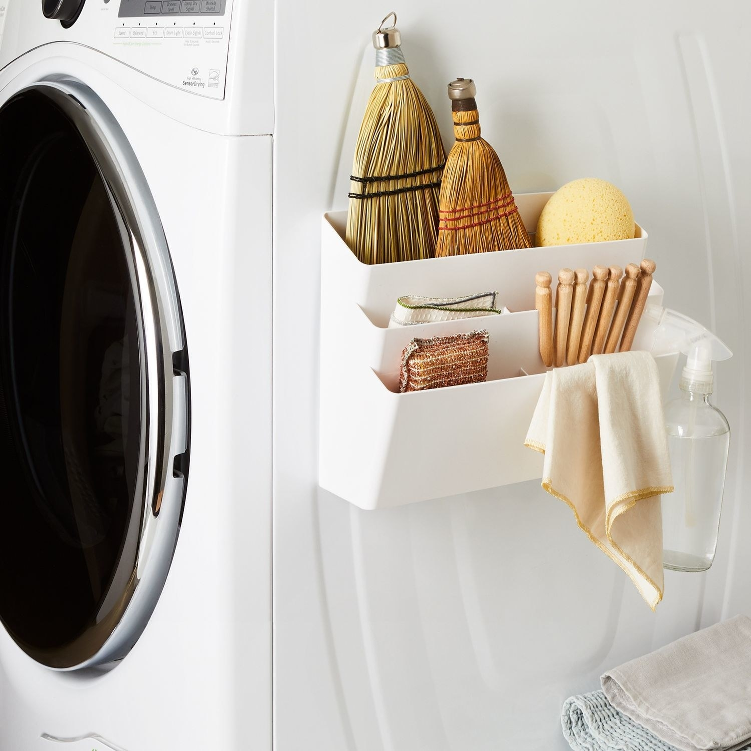 A white three-tier pocket on the side of a washing machine with assorted accessories in it