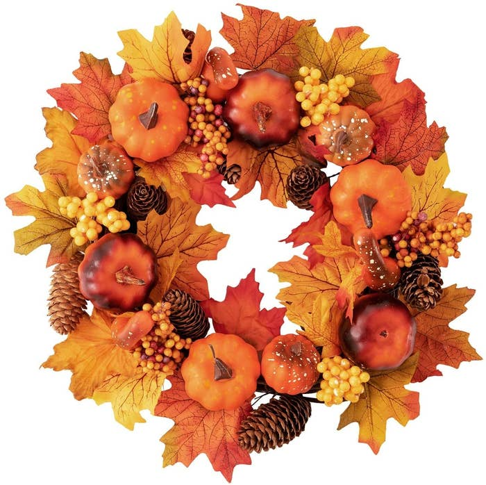 A wreath with autumn leaves pinecones and gourds