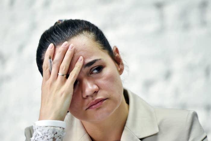 Svetlana Tikhanovskaya, with her hand on her forehead, looking very distraught