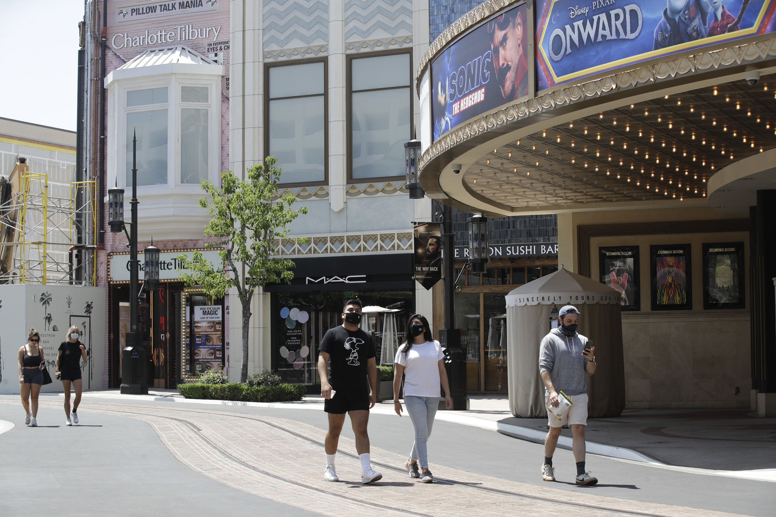 Five people, most wearing masks, walk down an otherwise empty outdoor street at the Grove outdoor mall