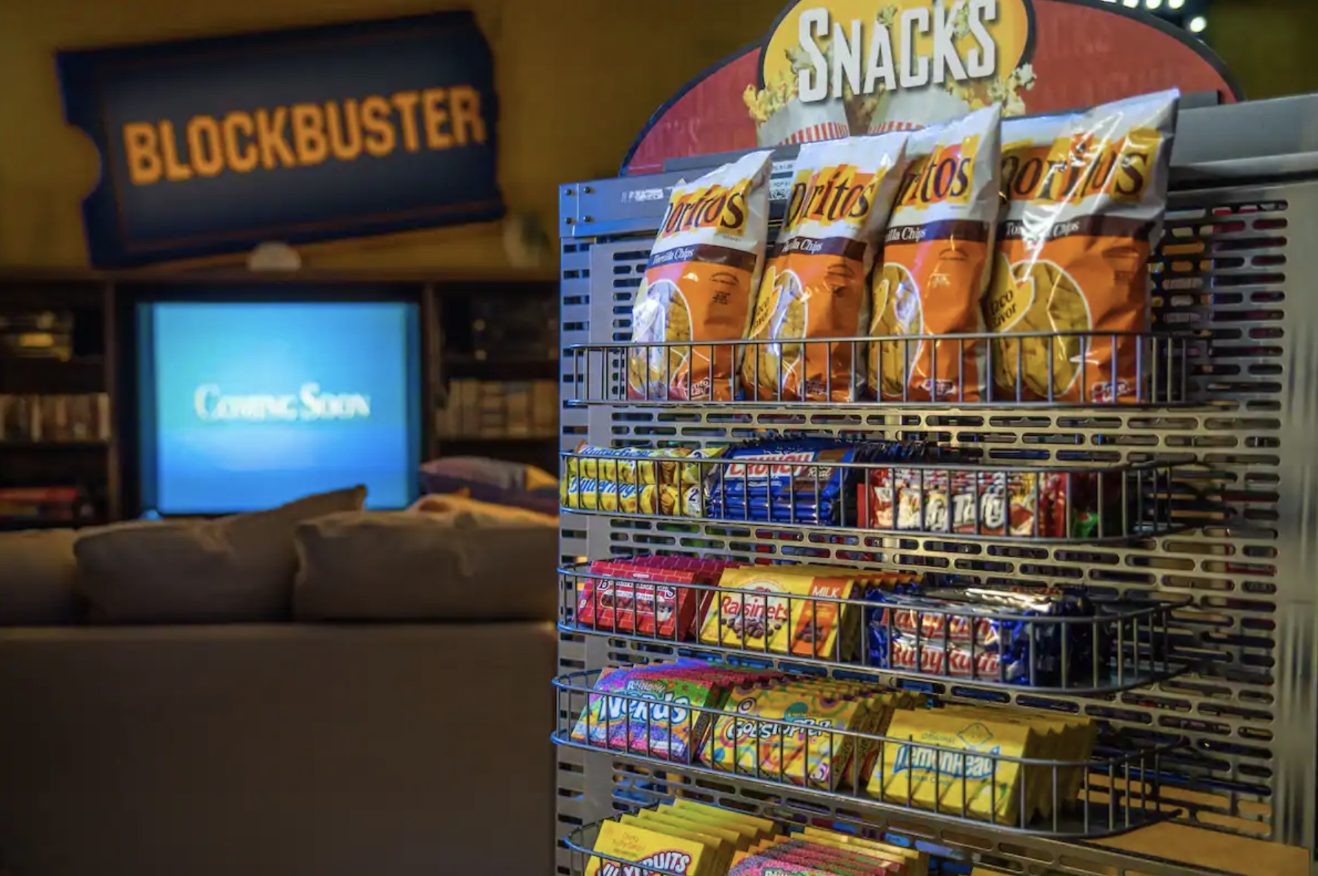 A rack filled with snacks like candy and chips next to the couch