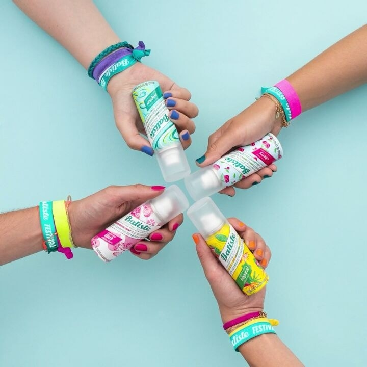 Four arms hold mini dry shampoo bottles in their hands against a bright background