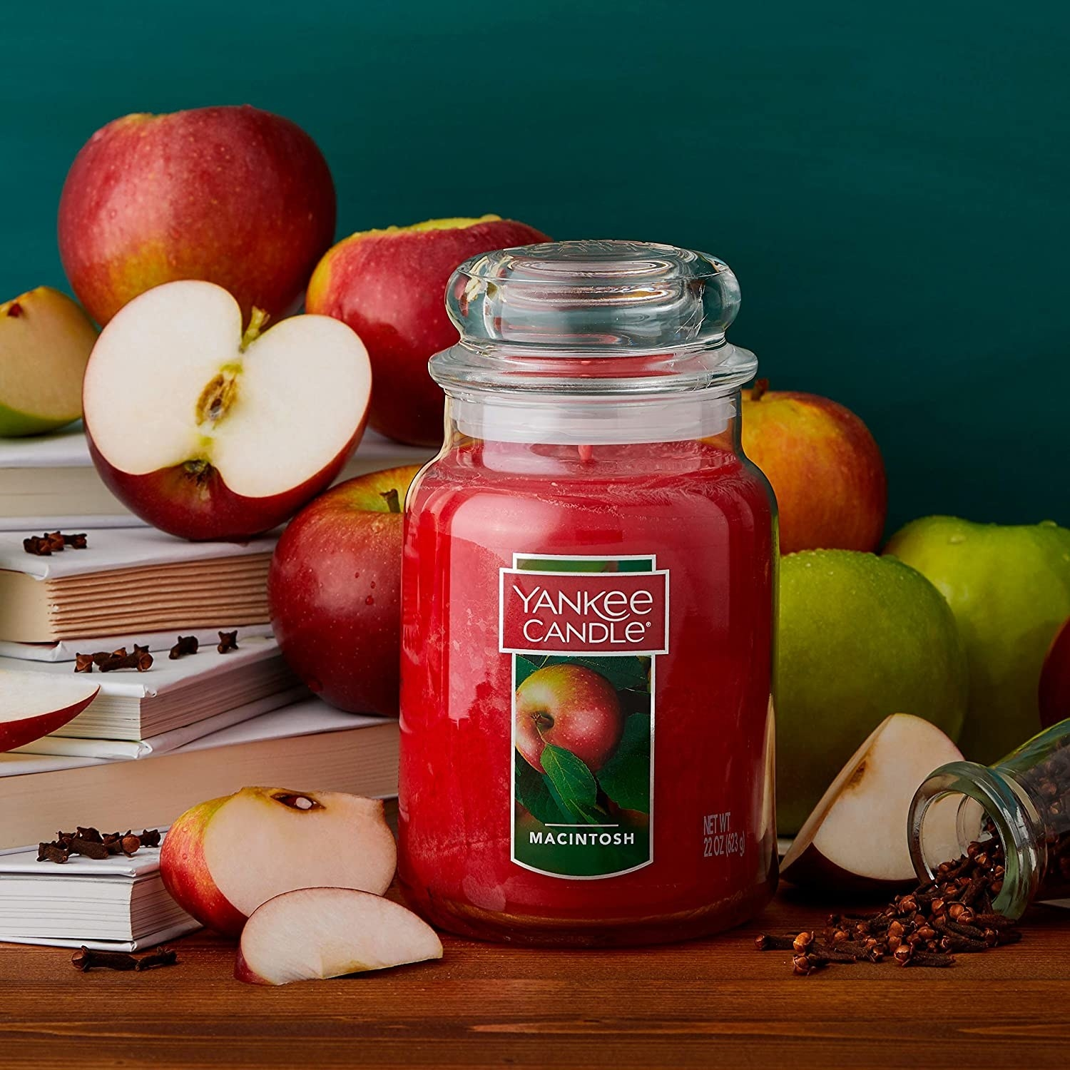 A candle with a lid and a macintosh apple on the front surrounded by applies and spices