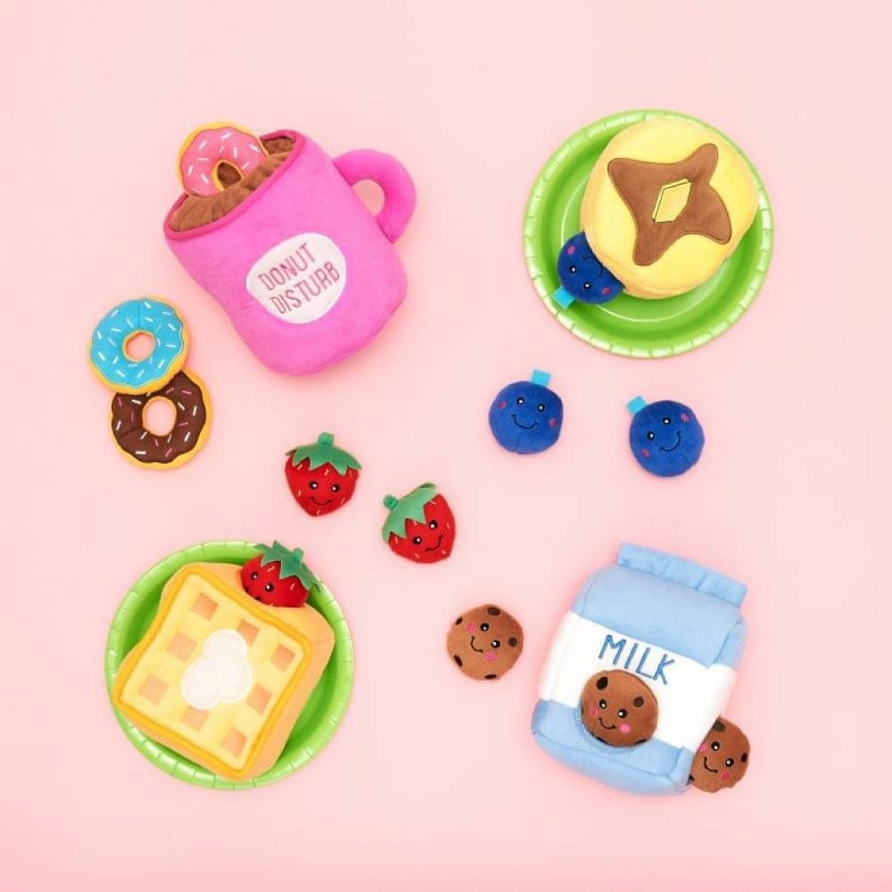 Assortment of the dog toys, including a milk carton, waffle, pancake, and donut in a mug