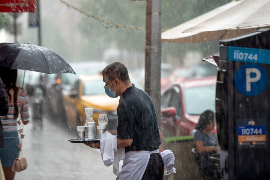 A server delivering drinks in the rain