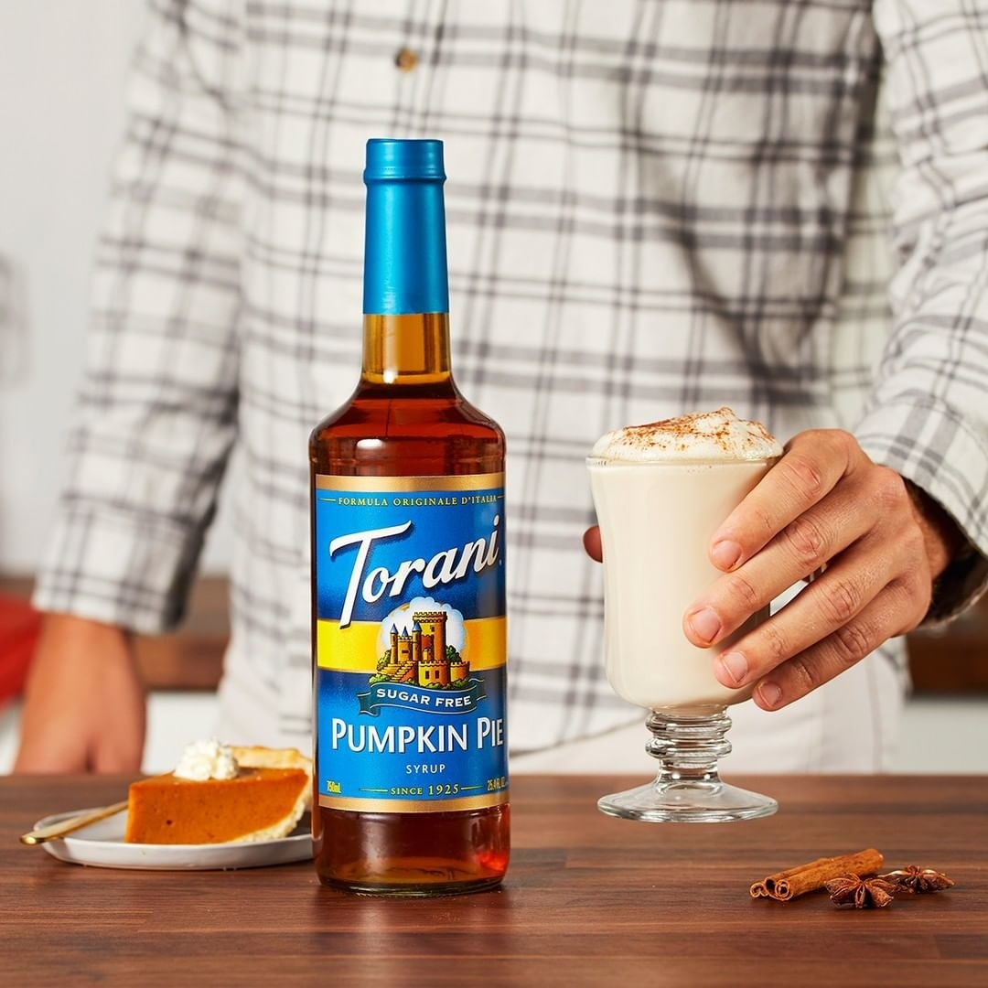 A person holding a drink with a bottle of the product on the table beside a slice of pumpkin pie