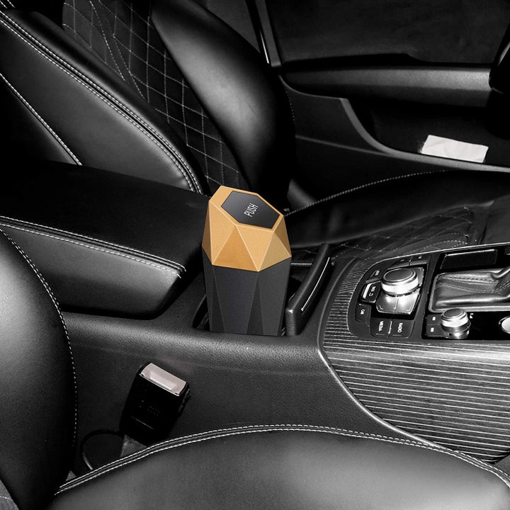 The mini trash can with geometric design sitting in the car's cup holders