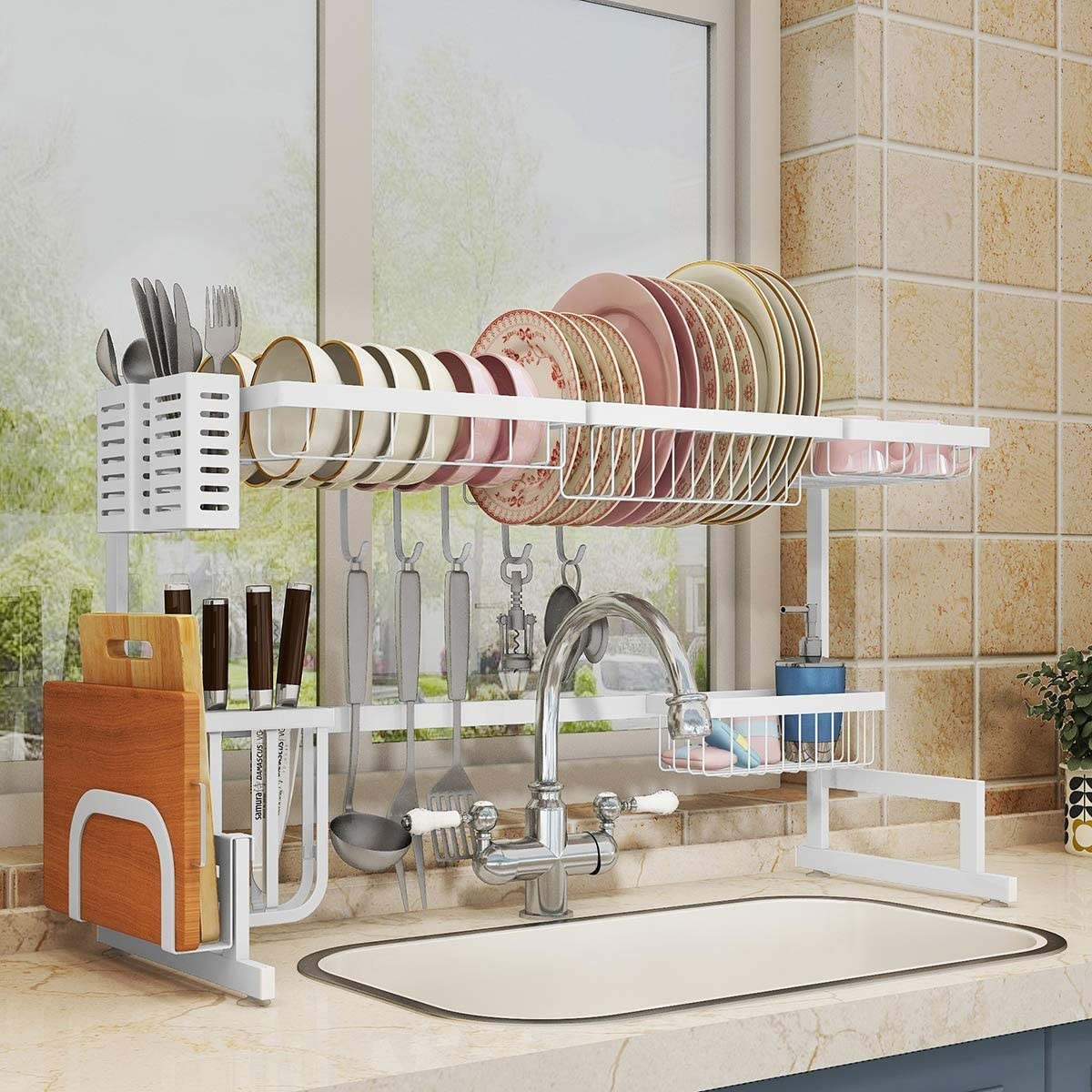 The drying rack above a kitchen sink with places to put bowls, plates, cups, silverware, cutting boards, knives, and other utensils