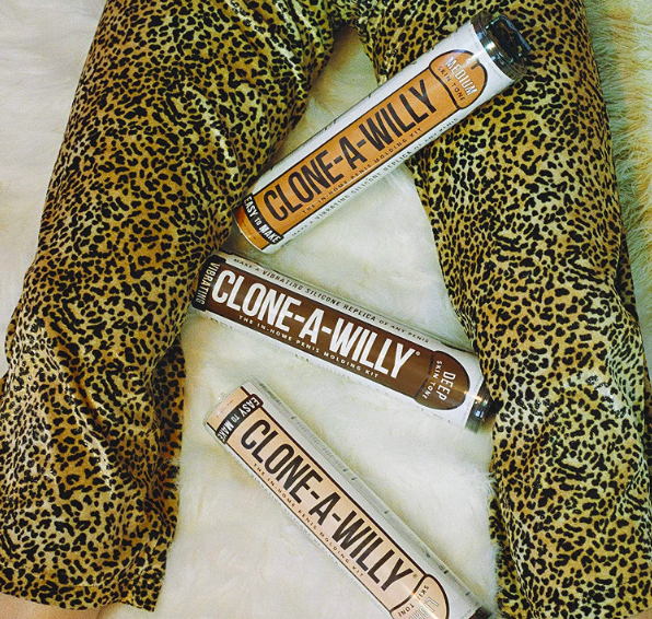 A person in leopard print pants with three Clone-A-Willy packages splayed out between their legs
