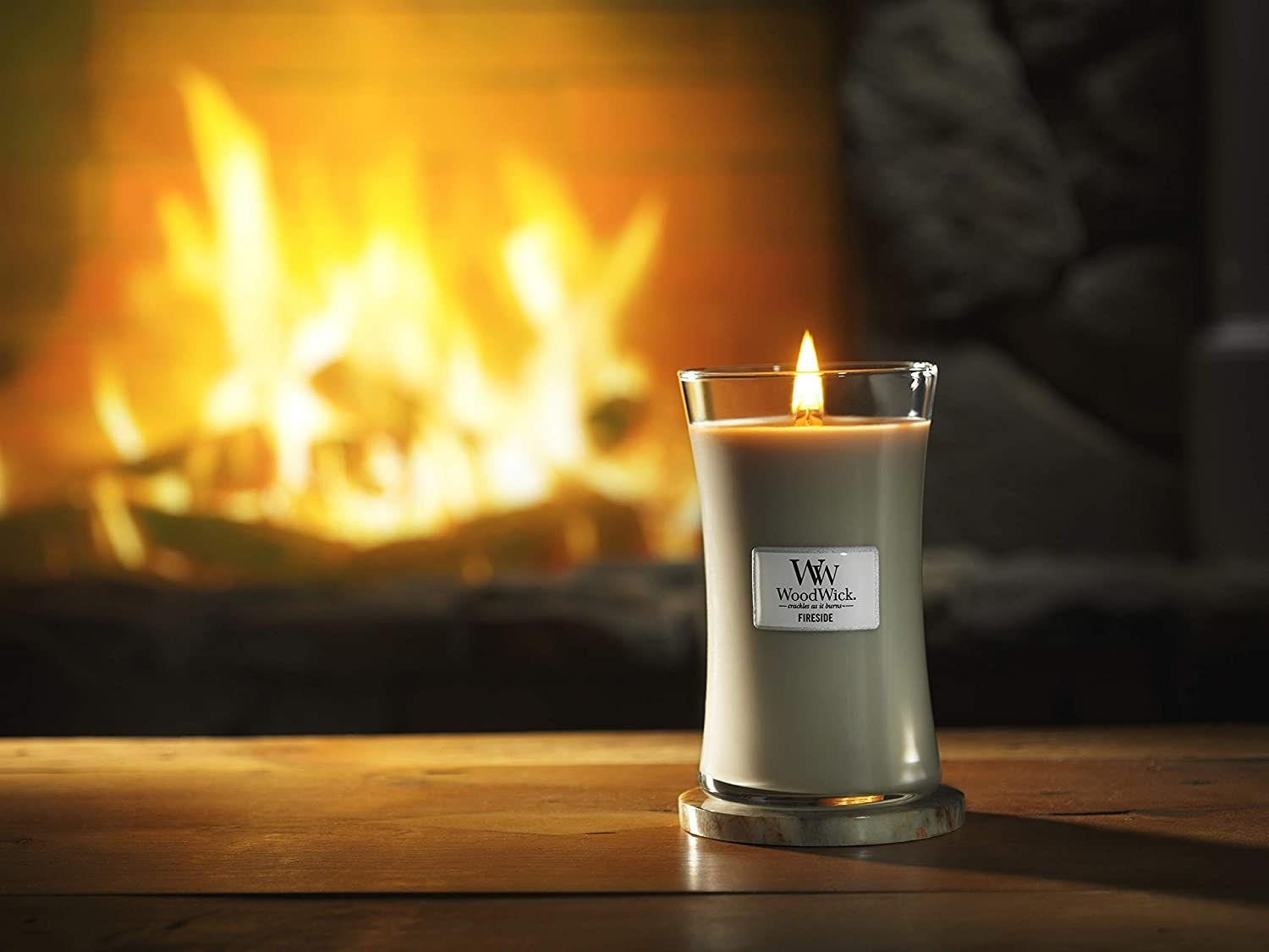 a green tall woodwick candle in front of a fireplace