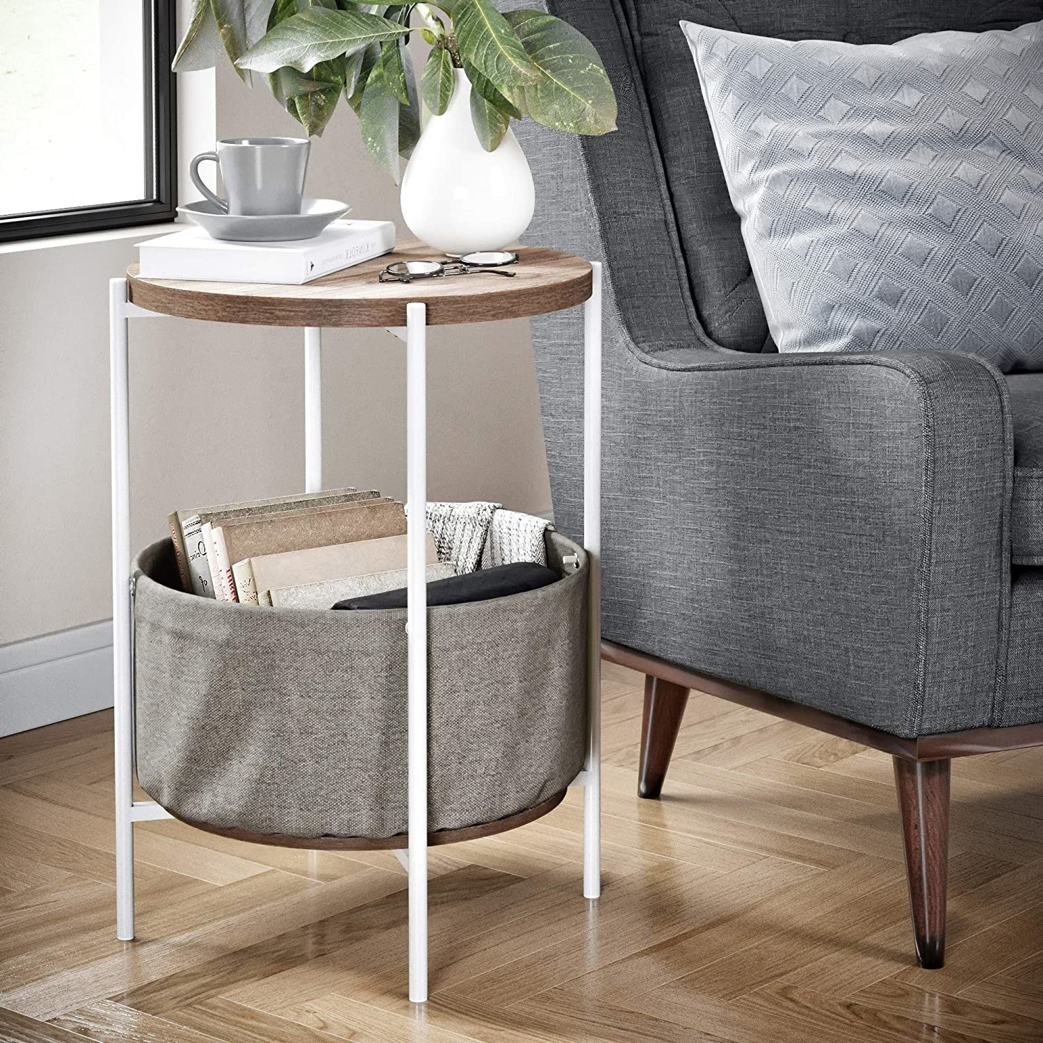 The circular side table with wood-like top, white legs, and a grey fabric bin with books and a blanket in it