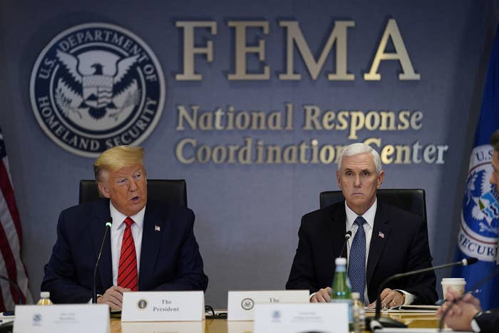 President Trump speaks while seated below the FEMA logo, with Vice President Pence by his side