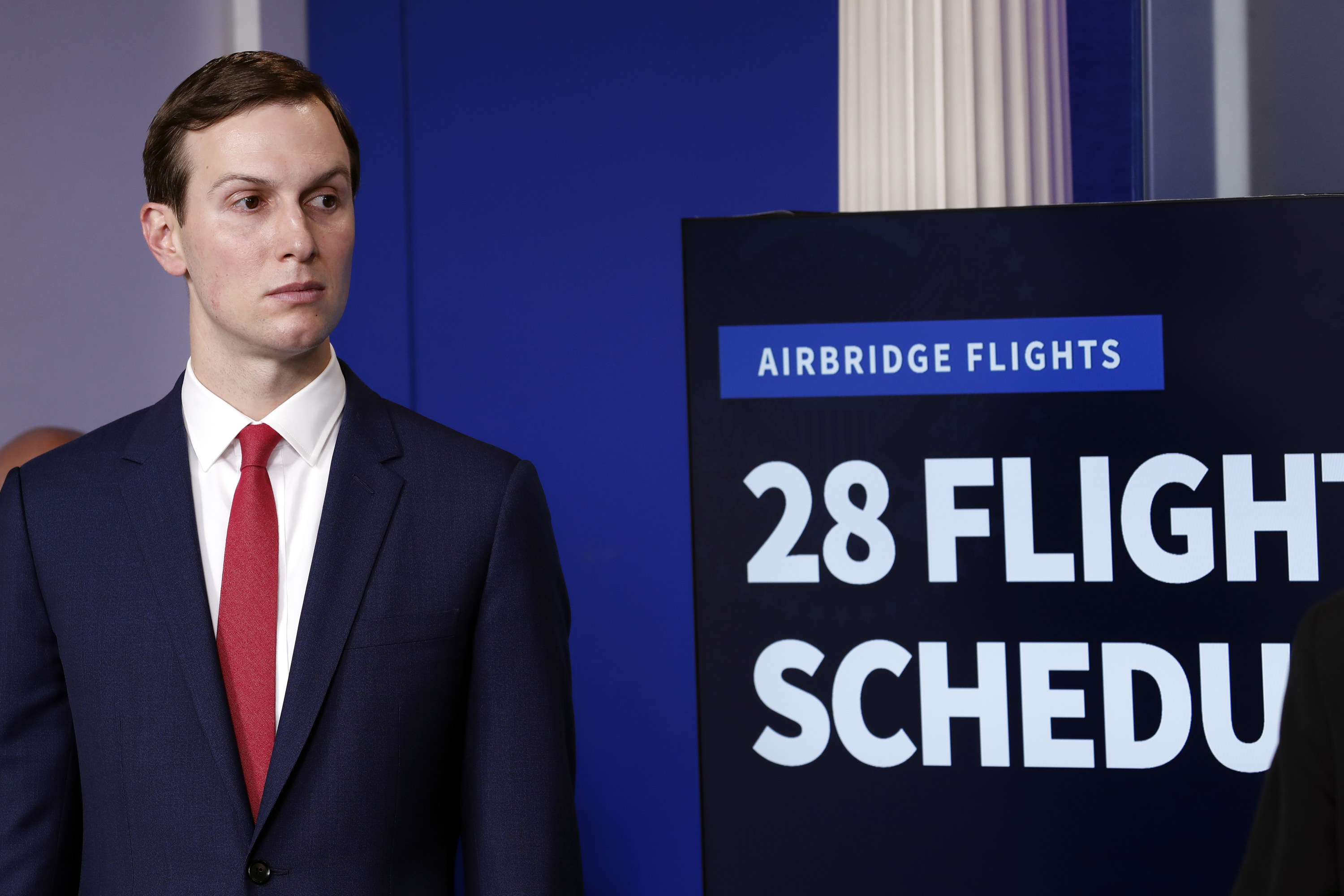 "Jared Kusher stands in front of a monitor that reads ""Airbridge Flights: 28 Flights Scheduled"""