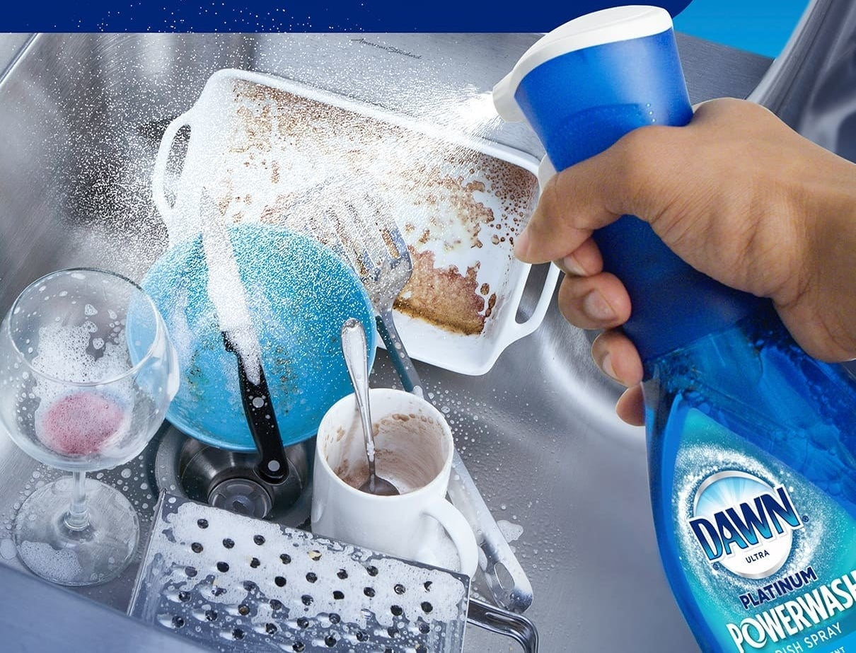 Hand holding the spray bottle of dish soap as it's being sprayed over a sink full of dirty dishes