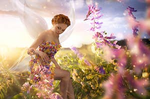 A fairy with a dress of flowers sitting in a meadow full of beautiful flowers