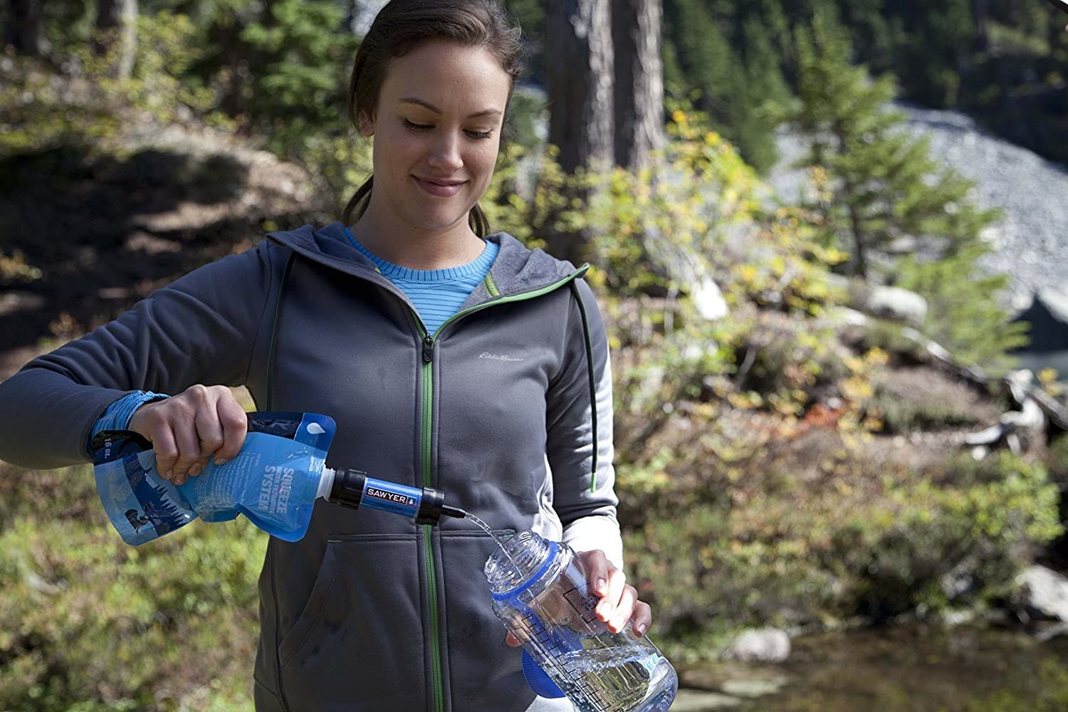 Model squeezing water from filtration straw and pouch into a bottle