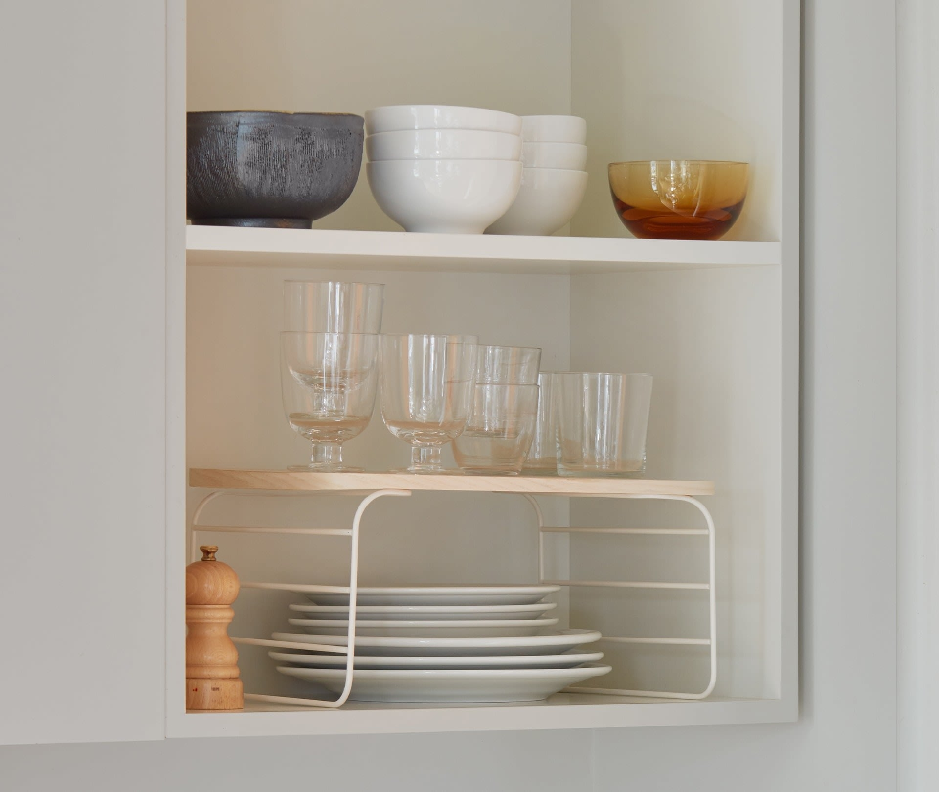 One shelf rises in a cabinet with plates underneath and glasses on top