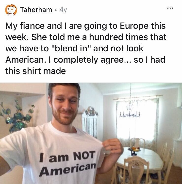 """A guy wearing a shirt that says, """"I am not American"""" despite being told by his partner to blend in and not look American on a trip"""