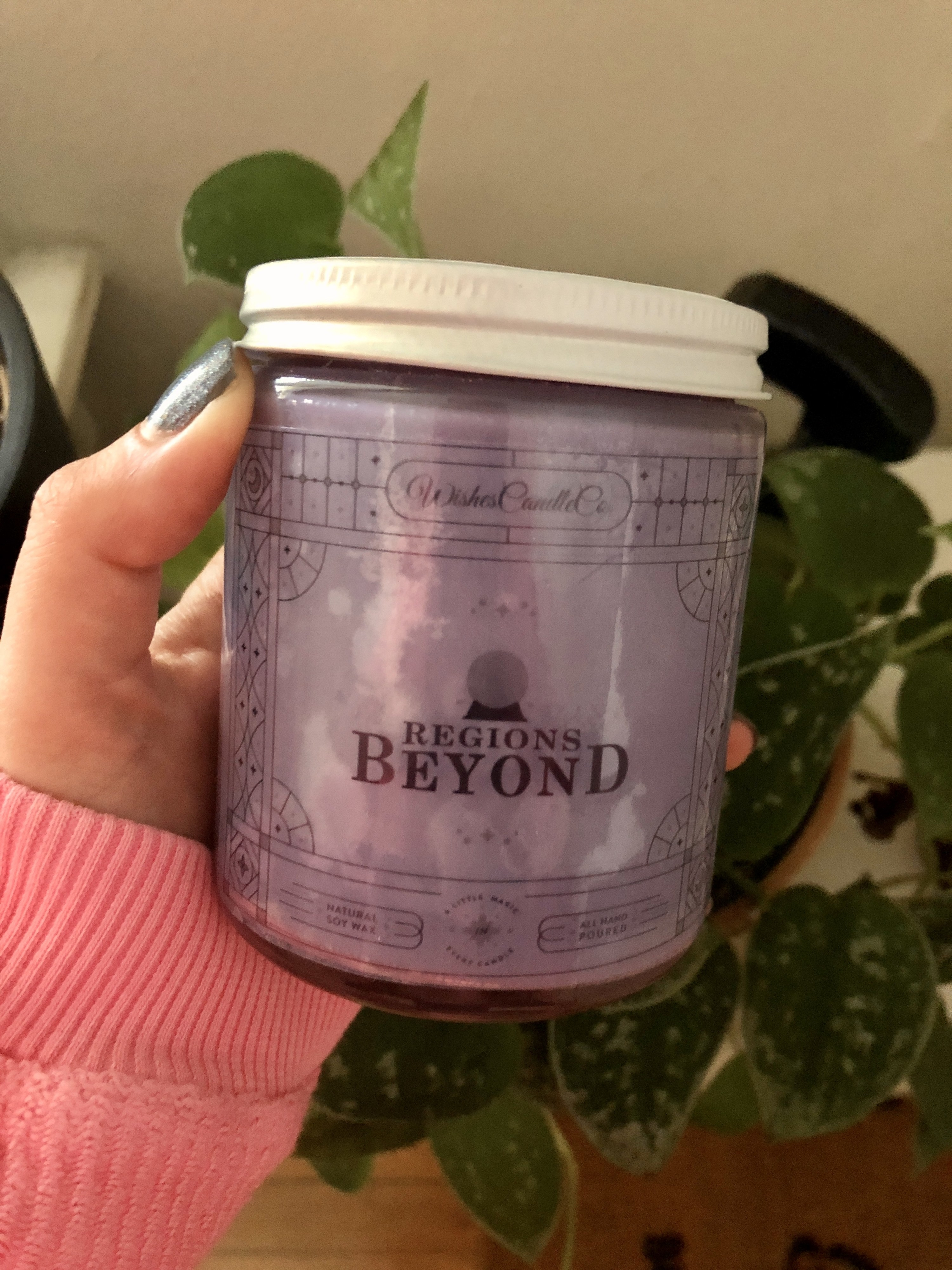 """a buzzfeed editor holding a glass candle with purple wax and """"regions beyond"""" written on it"""