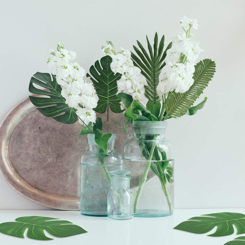 Fake tropical plant leaves in two vases on a table