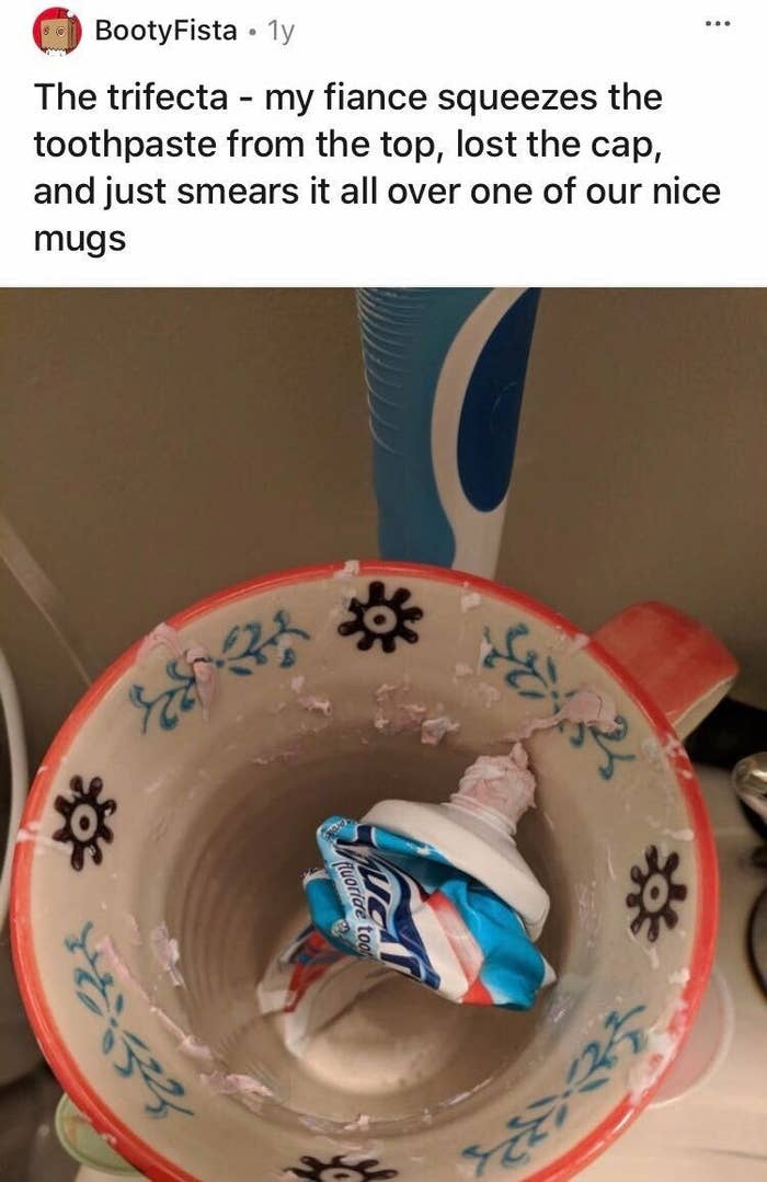 A nearly empty toothpaste bottle sitting in a ceramic cup smeared with residual toothpaste