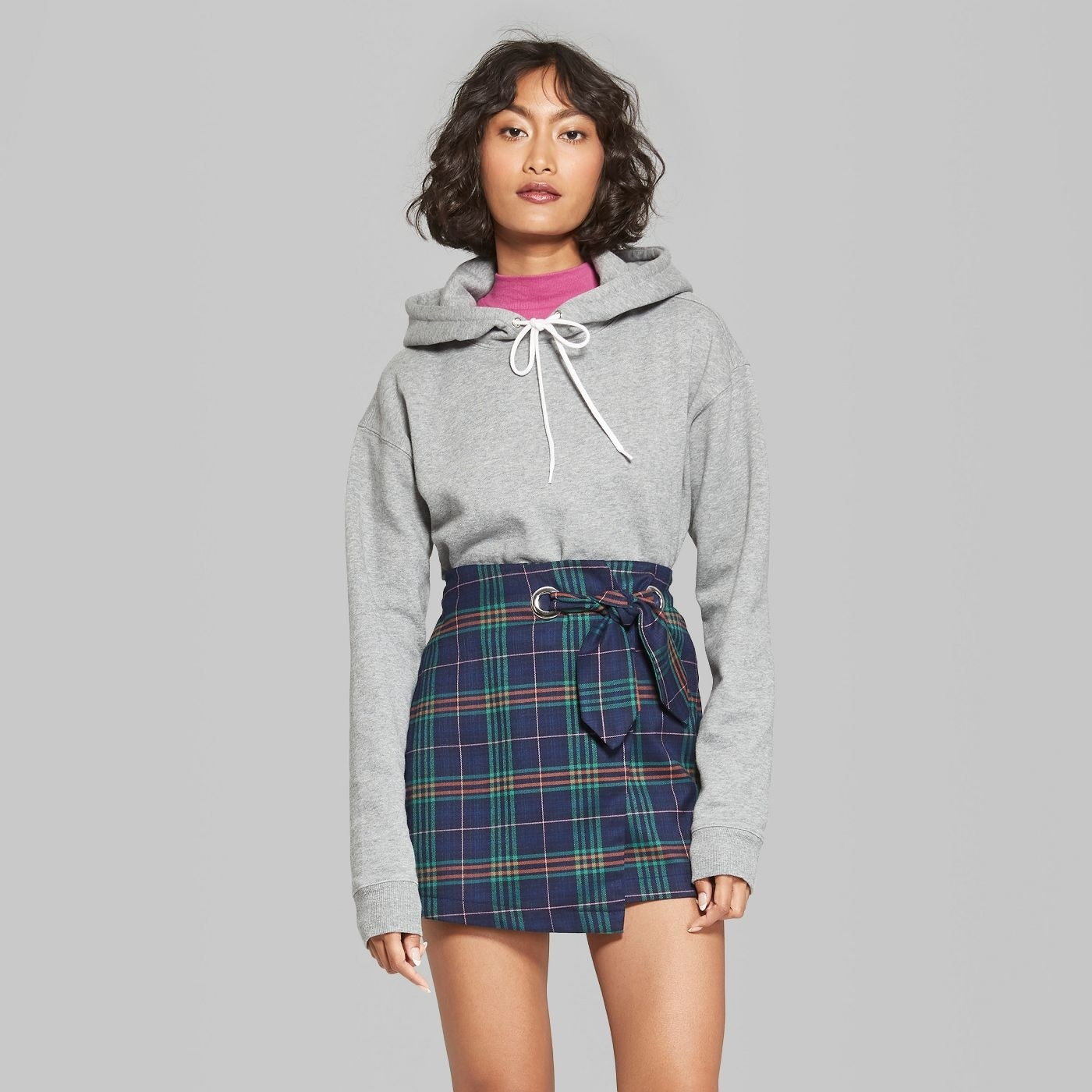 model wearing gray drawstring hoodie with skirt
