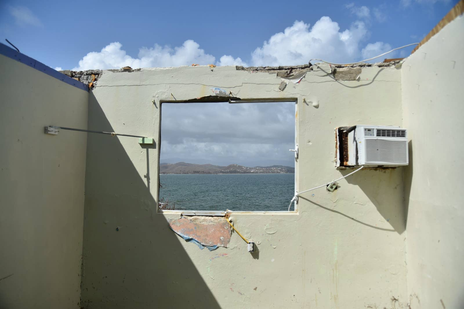 The wall of a house with no roof looks out onto the sea