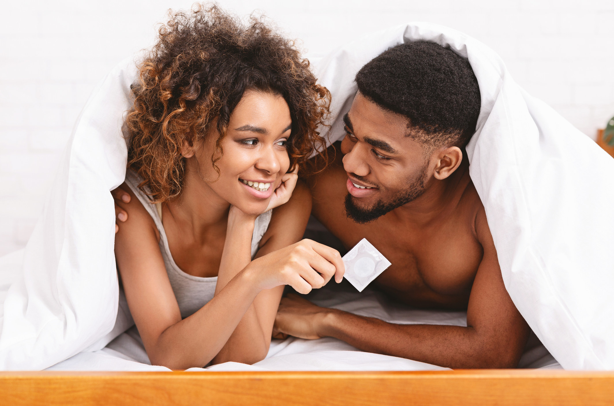 Photo of a couple in bed with a condom