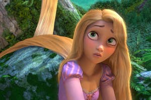 Rapunzel from Tangled with her long hair trailing behind her, draped over a pile of rocks
