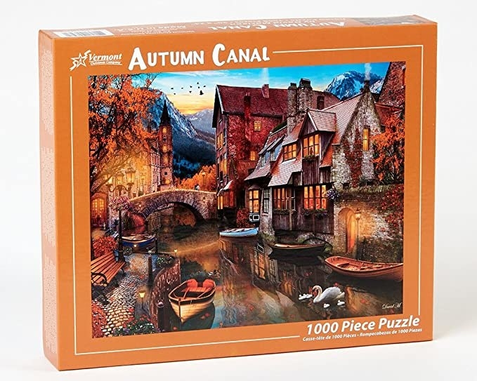 A box of a puzzle with a canal and warm lights and autumn leaves