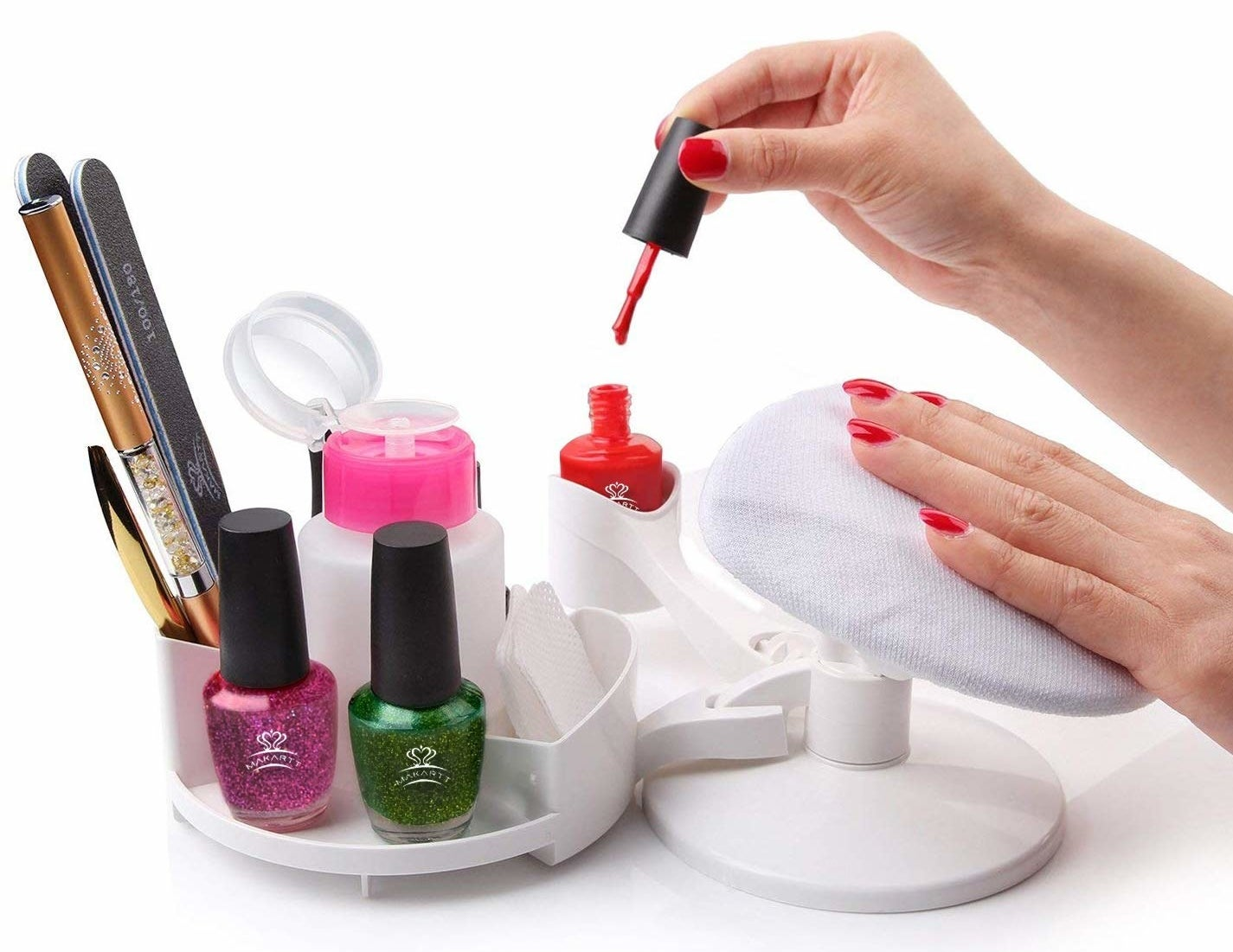 A person using the nail design pedestal to paint their nails.